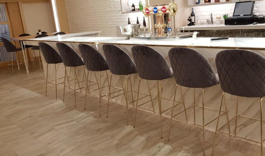 Taburetes en terciopelo con patas metálicas en dorado en barra de restaurante